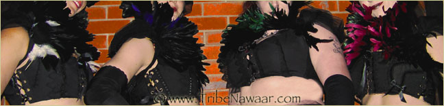 Tribe Nawaar wearing feather collars with reversed corseted bodice tops